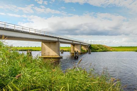 Betonnen brug in een landelijk gebied in Nederland. Het is een zonnige dag in het zomerseizoen met een blu hemel met enkele wolken.