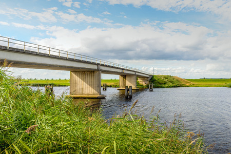 Concrete bridge in a rural area in the Netherlands. Its a sunny day in the summer season with a blu sky with some clouds. Stock Photo