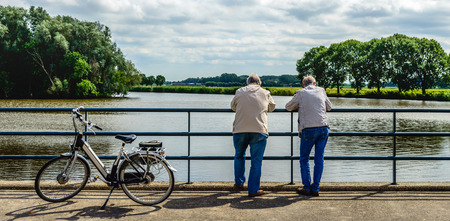 Two elderly men leaning over a bridge railing and looking musing over the water. Next to them an e-bike is parked. Stockfoto