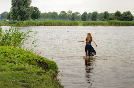 clothed: Young fully dressed woman walks into the water of a natural pond. Its a gray and gloomy day Stock Photo
