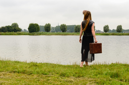 clothed: Young black dressed woman with garland of flowers in her hair and an old brown suitcase in her hand walks to the water of a natural pond. Its a gray and gloomy day Stock Photo