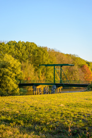 Green painted historic drawbridge from 1939 built across a creek in a Dutch nature reserve. It is a sunny day in the fall season. Stock Photo