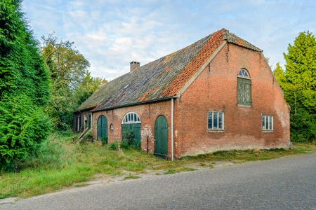 Abandoned and neglected historic long gable farmhouse built in 1885 in a small village in the Netherlands. Stock Photo