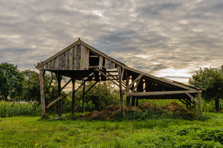 damaged roof: Backlit image of a neglected and abandoned old wooden barn for storing hay and straw. Its an early morning in the beginning of the autumn season.
