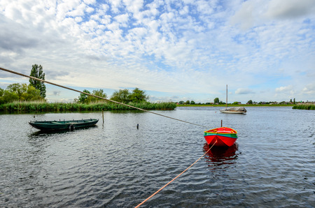 Brightly colored rowing boat moored with two ropes to a rusty iron pole in the water of a river in the Netherlands. Its the end of a cloudy day in the summer season.