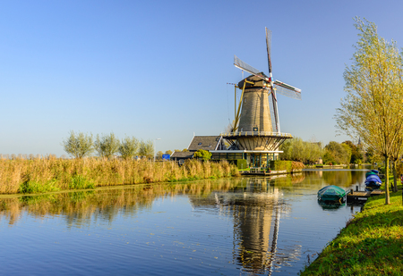 Dutch polder landscape near the village of Bleskensgraaf with a windmill and a canal  with some colorful covered boats on a sunny day in the fall season. Editorial