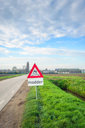 Traffic sign indicating mud in an agrarian landscape in Dutch. Its autumn and harvest time for sugar beets and a lot of mud is on the rural roads. Stock Photo