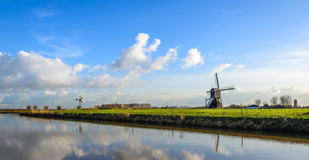 Panoramic image of a historic wooden holllow post mill and a small metal mill in a colorful lanscape in the Netherlands. Its a sunny day in the end of the Dutch winter season. Stock Photo