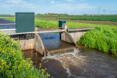 weir: Closeup of a small weir in a stream for water level control in a Dutch polder with high voltage lines and pylons in the background.