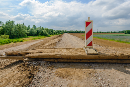 Road under construction closed with a wooden beam and a red and white road sign. The road is located on top of newly built Dutch dike. In the background is a field of cabbage cultivation.