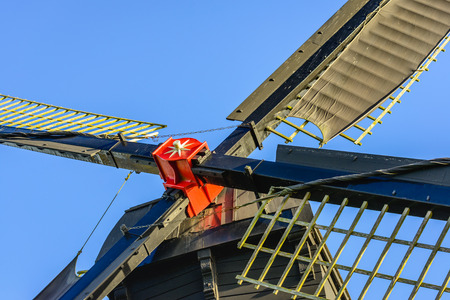 Closeup of a red painted windmill cross with sails against a blue sky. The hollow post mill was built in 1700.