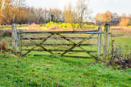 boundary: Old and crooked wooden gate near a nature area. The gate is closed and  and locked with a chain and padlock. Stock Photo