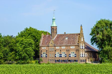Castle-like building in a rural setting in the Netherlands. The current building was built around 1936 on the site where originally was a real castle from the 14th century. This castle was destroyed by fire and the current building contains some elements  Stock Photo