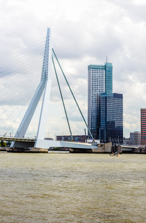 City view of Rotterdam with the Nieuw Maas river, the Erasmusbrug and skyscraper the Maastoren of 165 meters high on a cloudy day. The Maastoren is the tallest building in the Netherlands. The building was designed by Dam & Partners Architects and inaugur