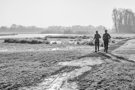 Monochrome backlit image of a man and a woman in  sportswear running hard early the morning of a sunny day in the winter season on an asphalt path in a Dutch landscape with frosty grass. Its cold outside now.