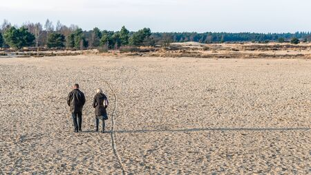 end of a long day: National Park in the Netherlands at the end of a clear day in the winter season. In the foreground a unknown man and woman walking in the sand. The low sun creates long shadows of them.