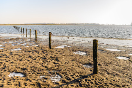 Fence of wooden poles and barbed wire diagonal in the image of a flooded area in the Dutch winter season. Lizenzfreie Bilder