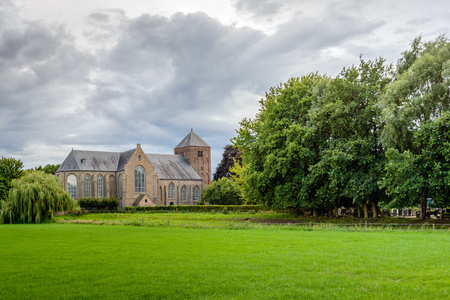 Bedrohliche Wolken bedrohlich über eine alte holländische Kirche in einer ländlichen Umgebung in der Sommersaison. Lizenzfreie Bilder