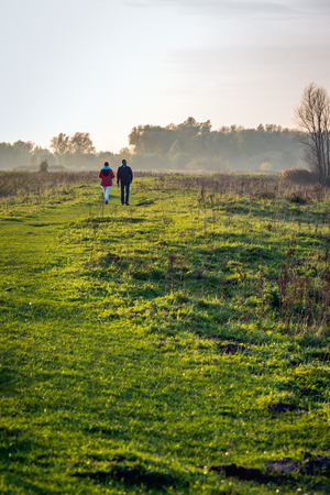 and hiking path: A man and a woman walking together in a Dutch nature reserve. It is at the end of an autumn day, the sun is low and theres some haze in the distance across the landscape.