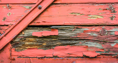 Part of an old and weathered railway wagon with flaking red paint.