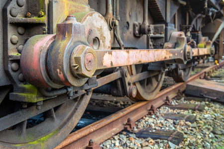 Closeup of the weathered drive mechanism of an old diesel-electric locomotive parked on rusty rails in the Netherlands. Lizenzfreie Bilder