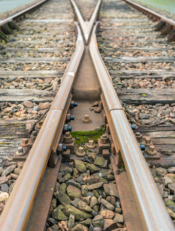 Closeup of intersecting railway lines of rust-colored rails supported on timber sleepers laid on crushed stone ballast.
