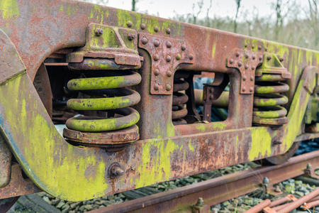Weathered chassis of an old freight railroad car with large shock absorbing steel springs.