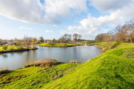 Uitzicht op het pittoreske Nederlandse vestingstadje Woudrichem op een zonnige en bewolkte dag in het herfstseizoen.