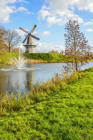 Achthoekige graanmolen Nooit Gedagt met zeilen aan de rand van het Nederlandse vestingstadje Woudrichem in de provincie Noord-Brabant. Het is nu een zonnige dag in het herfstseizoen. Stockfoto