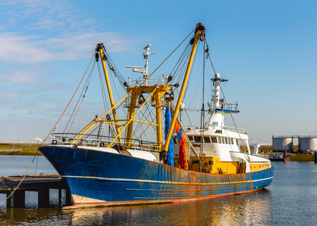 Modern Dutch trawler moored at a wooden jetty in a fishing port Stock Photo