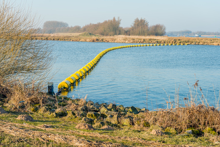 Geel drijft als een scheidslijn in het water van een Nederlands meer aan het einde van het winterseizoen. Stockfoto