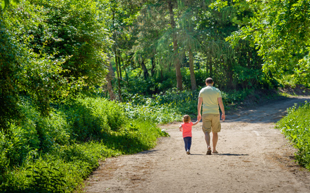 Father and his little daughter walking hand in hand together on a sandy path in the forest. It is a warm and sunny day in the spring season. Lizenzfreie Bilder