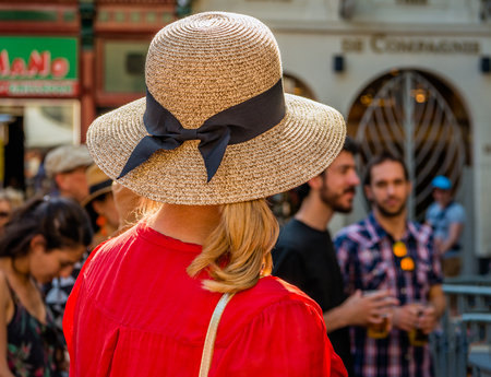Backside of an unidentified elegant blonde woman with a straw hat with a black ribbon and a bright red shirt. She looks at the two young men in front of her.