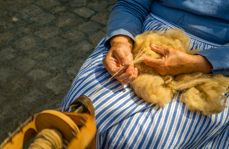 Closeup of female hands spinning raw sheep wool on a spinning wheel Lizenzfreie Bilder
