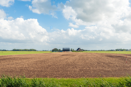 Overview of a modern Dutch farmhouse with barns and cultivated soil in front of it. It is a cloudy day in the spring season.