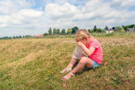 Meisje met blonde vlechten kijkt in een plastic zak naar de gekleurde snoepjes onderaan terwijl ze op de helling van een dijk zit tijdens een korte stop in een wandeling door een Nederlands natuurreservaat. Stockfoto - 81242783