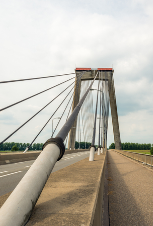 heavy: Closeup of the cable of a cable-stayed bridge over the river Bergsche Maas near the village of Heusden in North Brabant, Netherlands. It is a cloudy day in the summer season.