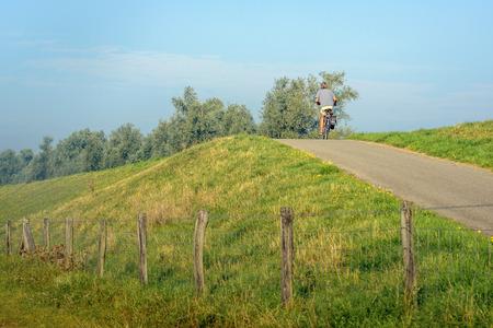Onbekende man fietsen op de top van een dijk op een zonnige dag in het Nederlandse zomerseizoen. Stockfoto - 85111686