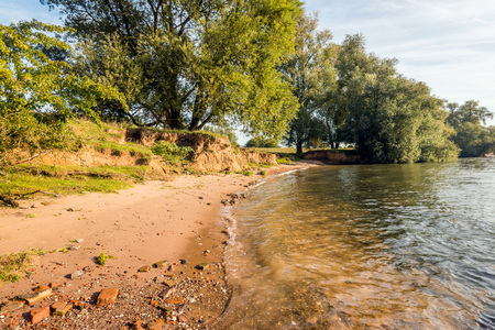 Bank of the wide Dutch river Waal early in the morning on a sunny day in the beginning of the fall season. Lizenzfreie Bilder
