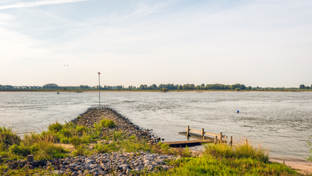 Groyne of basalt stones and a small wooden jetty in the wide Dutch river Waal. Its in the beginning of autumn, two geese are flying. Lizenzfreie Bilder