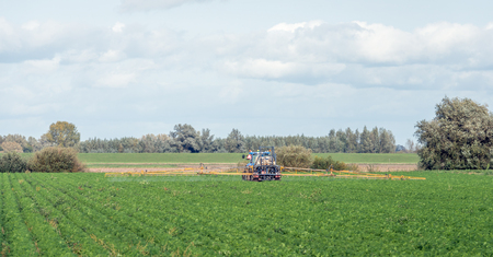 A field sprayer system in open configuration  attached to a tractor sprays the carrot leaves in the field against the carrot fly insects. Lizenzfreie Bilder