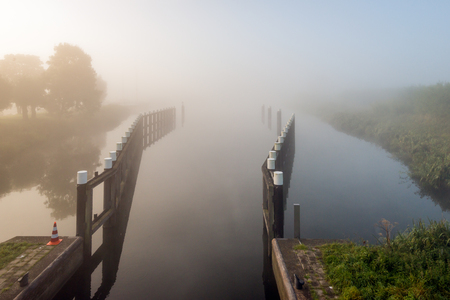 Wooden fencing as part of a small sluice in the Netherlands. It is a foggy morning in the beginning of the fall season. Lizenzfreie Bilder