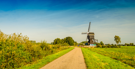 Picturesque panoramic image of a Dutch country road with a wooden hollow post polder mill from 1762, restored in 1953. The mill is now a national monument and no longer in use as a polder mill.