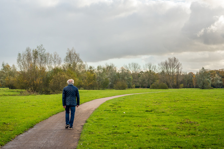 Older man with gray hair walks over a curved footpath through the park on a cloudy day in the fall season. Lizenzfreie Bilder