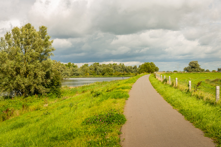 Threatening clouds above a Dutch polder landscape with a narrow path on the top of an embankment next to a river. In the background a small boat is visible in the river.