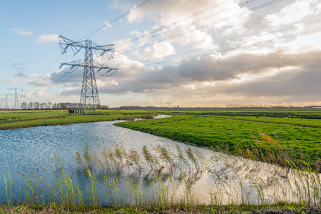 Backlit image of high-voltage lines and pylons in a Dutch polder landscape. In the middle of the horizon the chimneys and the cooling tower of the power station are just visible.