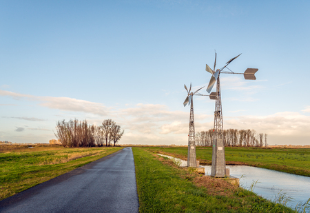Small wind-powered watermills in a Dutch polder regulate the water level in the ditches fully automatically.
