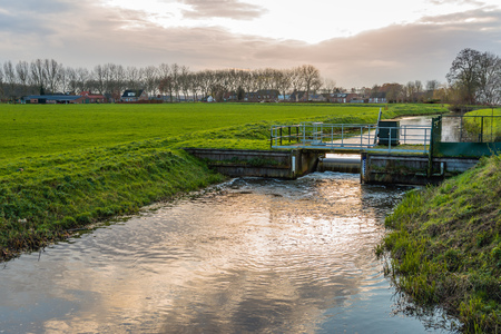 Backlit image of a Dutch polder in the fall season. The small weit regulates the water level in the ditch. Banco de Imagens - 91386652