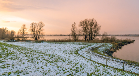 Sunset at a Dutch river in the winter seaon. Bare trees contrast against the orange and pink sky. There is still some snow. Stock Photo