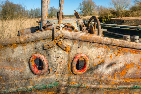 Close-up of the bow of a weathered and rusted old iron ship moored in a Dutch river.